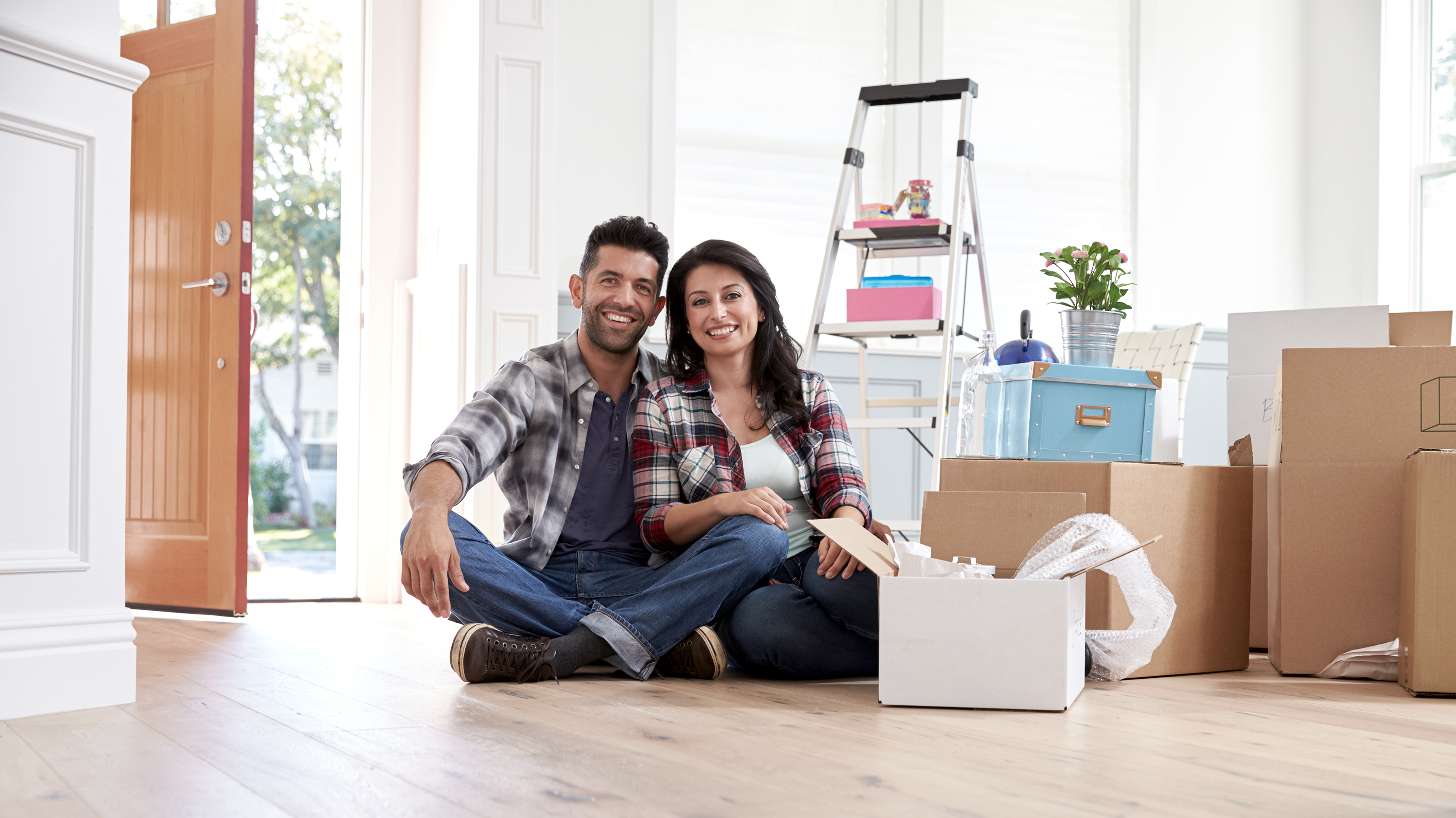 Portrait Of Hispanic Couple Moving Into New Home